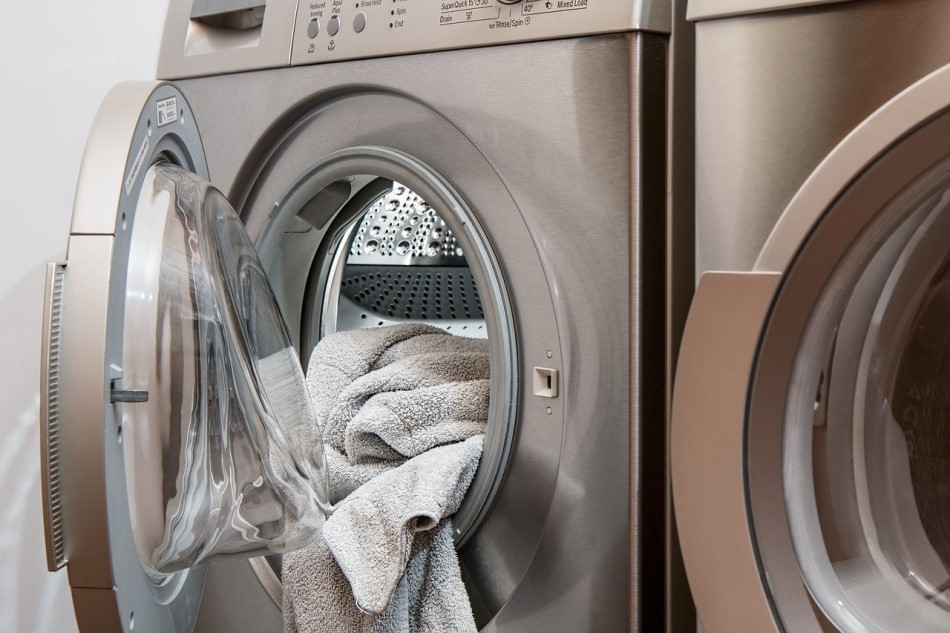 Stock image of a washing machine with an open door and laundry hanging out of it