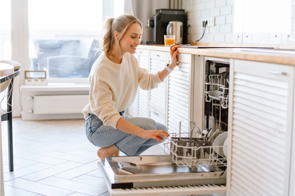Smiling young white woman putting dishes in the dishwasher at home
